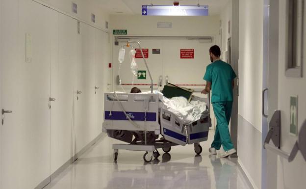 Paciente en camilla en hospital llevado por enfermero